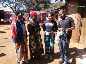 Myself (second from right) and Blessings, a field team member (far right), explaining how a CDC mosquito light trap operates to two local women before installing it in their houses for one of the ongoing Blantyre Malaria Project studies.